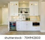 wet bar with white cabinets... | Shutterstock . vector #704942833