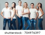 Small photo of Happy together concept. Group portrait of healthy boys and girls in white t-shirts, sleeveless shirts and blue jeans standing and posing over gray background. Urban style. Studio shot