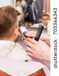 little boy getting haircut by... | Shutterstock . vector #705366343