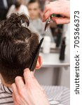 young man getting haircut by... | Shutterstock . vector #705366373