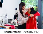 asian tailor adjusts garment... | Shutterstock . vector #705382447