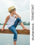 a boy in a straw hat sitting on ... | Shutterstock . vector #705407347