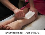 beautician applying wax to females leg to remove hair - stock photo
