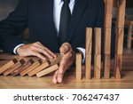 Small photo of Close up of businessman hand Stopping Falling wooden Dominoes effect from continuous toppled or risk, strategy and successful intervention concept for business.