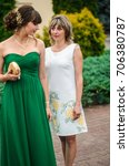 Small photo of Prom. Photos with parents . Girl in evening dress green