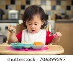 baby girl eating vegetable at...   Shutterstock . vector #706399297