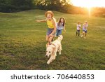 Stock photo happy multiethnic teens walking with golden retriever dog in park 706440853