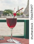 Small photo of Fresh up with drink - cranberry juice - in restaurant by the river with famous tourist attraction background of Wat Arun ,Bangkok, Thailand