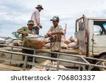 Small photo of SIHANOUKVILLE, CAMBODIA - 7/20/2015: Cambodian laborers offload bags of Ammonium Sulphate Fertilizer in a small fishing village.