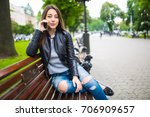 young woman sitting on a bench... | Shutterstock . vector #706909657