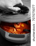 Small photo of Man lifting lid on a chicken paprika casserole with selective color