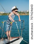 Small photo of Experienced funny little boy captain wearing captain hat and fashionable sunglasses on board of luxury boat in summer cruise around the world