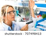 Small photo of Young attractive female scientist with protective eyeglasses examining DNA autoradiogram test results in the scientific biochemical laboratory