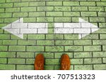 Small photo of Person's feet in suede shoes is standing at tile green pavement crossroad with white arrows print pointing in two different directions. Two ways to choose making decision which way to go. Top view