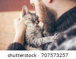 Stock photo muzzle of a cat and a mans face close up of handsome young man and tabby cat two profiles the 707573257