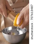 Small photo of Man extracting lemon juice with wooden citrus reamer