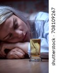 Small photo of Portrait of young blonde woman sitting at home and drinking beer. Female alcohol addiction.