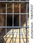 Small photo of Black deep hole pit with stone walls covered with steel cage under day sunlight to deny access to restricted area and protect human lives