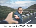 Small photo of Young laughing girl outstretching hand asking to follow her on background of mountain road, Iceland, West Fjords.