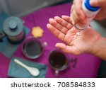 Small photo of Woman putting sweetener tablets from a dispenser into her hands, and adding them to cups of coffees.