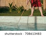 Small photo of staff using tool cleaning swimming pool to maintain water clean.