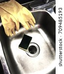 Small photo of Close up of a clean kitchen sink with yellow rubber gloves and sponge after the dishes are cleaned.