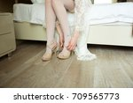 the bride adjusts the shoe on... | Shutterstock . vector #709565773
