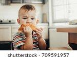 wonderful little child eating a ... | Shutterstock . vector #709591957