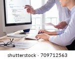Stock photo team of web app developers coding website source code and debugging on computer screen before 709712563