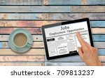 Small photo of Online job hunting Hand with computer tablet reading employment ads on table with coffee