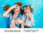 Small photo of Brightful stylish image from above excited mother and daughter laying on blue floor in popcorn, laughing in 3D glasses. Happy family time, entertainment pretty mum with kid, expressing happiness