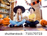 Small photo of Sweets for us! Treat or trick! Very cheerful excited small kids in carnival head wear, with colorful treats, carved pumpkins, fall leaves, orange papers near them on the brown wooden floor