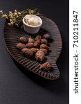 Small photo of Shea butter nuts and cup of shea butter. Black background