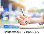 woman's hand writing on a... | Shutterstock . vector #710230177