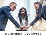happy colleagues putting hands... | Shutterstock . vector #710459653