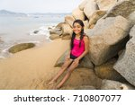 Beautiful young girl brunette with long wet hair is sitting on the rocks in coastline