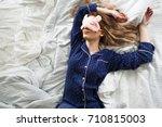 cute blonde in her bed in blue... | Shutterstock . vector #710815003