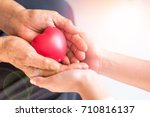 Small photo of Philanthropy health care concept. Caregiver with senior people hands with heart in palm in hospice center with copyspace.