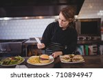 confident young waiter holding... | Shutterstock . vector #710894947