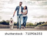Stock photo romantic couple is on a walk in the city with their dog labrador beautiful young woman and 710906353
