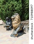 Small photo of A bronze statue of an aggressive lion adorns the avenue in the park.