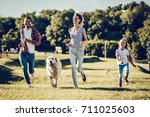 Stock photo beautiful happy family is having fun with golden retriever outdoors mother father and daughter 711025603