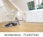 woman seated on wooden floor | Shutterstock . vector #711027163