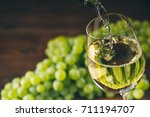 pouring white wine into a glass ... | Shutterstock . vector #711194707
