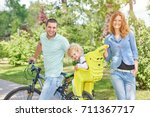 beautiful happy family cycling... | Shutterstock . vector #711367717