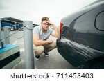 sad man standing near car with... | Shutterstock . vector #711453403