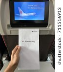 """Small photo of 7th Sept 2017 : HANOI,VIETNAM : """"Man's hand holding white air sickness bag.Media Player on aircraft seat background"""""""