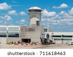 Small photo of ORLANDO, USA - AUGUST 19th, 2017: Image of a control tower and departure gate airbridge at Orlando Airport. Florida, USA