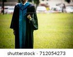 hand of graduate holding black... | Shutterstock . vector #712054273