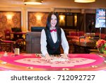 cute lady casino dealer at... | Shutterstock . vector #712092727